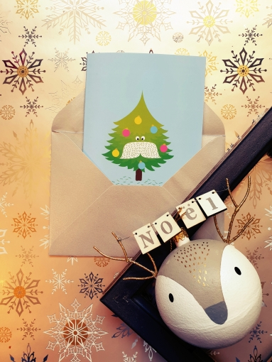 """Carte """"Sapin moustachu"""" dans une enveloppe argentée, avec un cadre et une boule de sapin """"cerf mignon""""."""