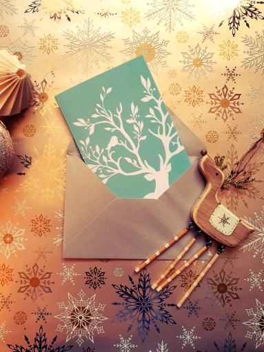"""Carte """"cerf et oiseaux sur fond bleu clair"""" dans une enveloppe argentée, avec un petit cerf en bois et des boules de Noël à côté."""