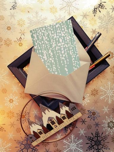 """Carte """"Cascade de guirlandes de Noël sur fond bleu clair"""" dans une enveloppe argentée, posée sur un cadre avec deux stylos et une décoration de Noël."""